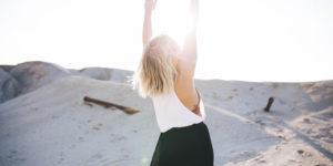 Femme blonde en plein désert qui lève les mains vers le ciel